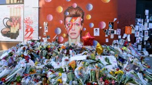 BRIXTON LONDON UNITED KINGDOM- January 28 2016: Flowers left beneath a mural as fans paying tribute to David Bowie in his birthplace. Bowie was born as David Robert Jones in Brixton London UK.