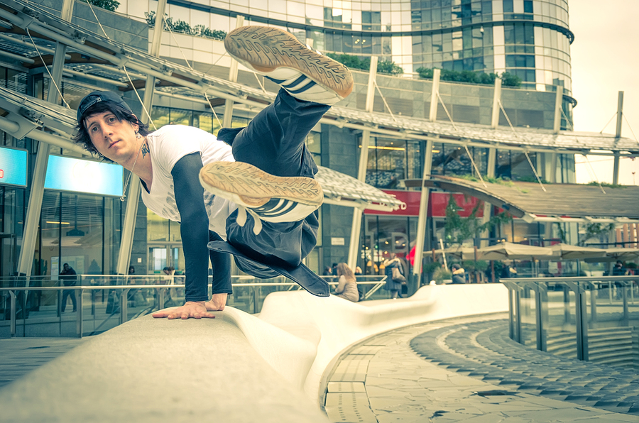 Parkour athlete jumping over a handrail - Free runner performing tricks in a urban settlement - Parkourfree runningyouthsport and lifestyle concept