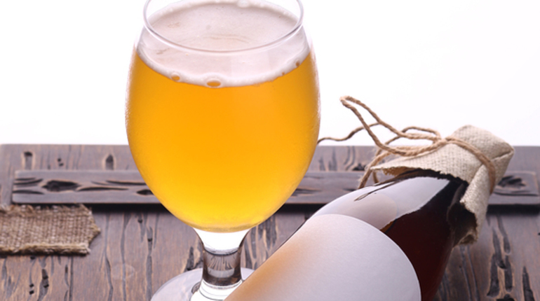 Bottle with blank label template and glass of home brewed craft beer standing on a wooden chest with bright white background