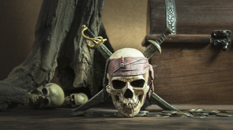 pirate skull with two swords and coffer over two head of human background still life style pirate concept for halloween