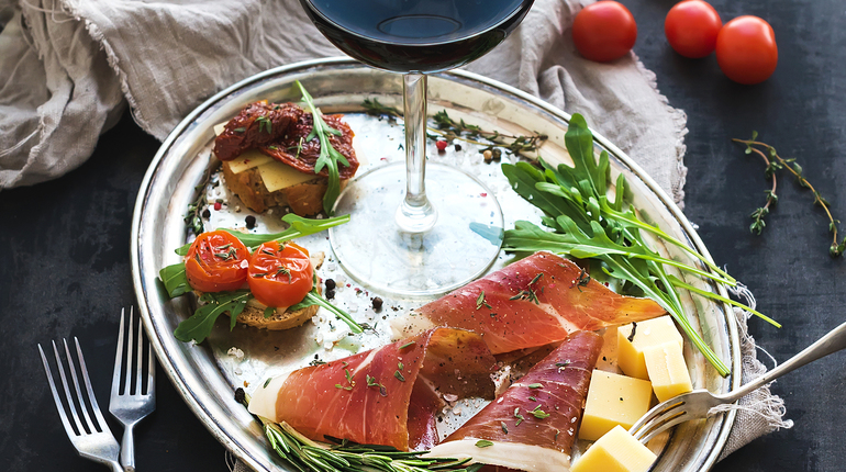 Wine appetizer set. Glass of red wine, vintage dinnerware, brushetta with cherry, dried tomatoes, arugula, parmesan, smoked meat on silver tray over rustic grunge surface. Closeup